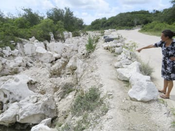リン鉱石を採掘した跡地を指さすジュリーさん=9月、ナウル(共同)