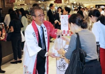 来客に新之助の新米を配ってPRする花角英世知事=10日、東京・新宿
