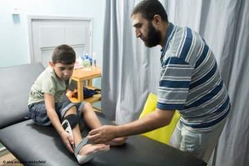 リハビリに訪れた父子。イスラエル軍の発砲で息子は膝を損傷、父親は親指を切断した