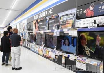 家電量販店のテレビコーナーで品定めをする客
