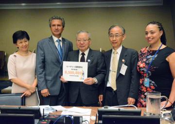 10日、ニューヨークの国連本部で国連総会第1委員会のジンガ議長(左から2人目)に署名の目録を手渡した被団協の木戸季市事務局長(中央)(共同)