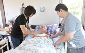 サクションで痰を取り出してもらっている西澤治廣さん(中央)。「災害弱者」にとって停電は命に関わる問題だ