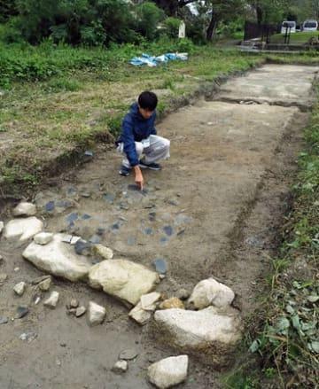 発掘された大溝城本丸(写真左側)と二の丸(右側)をつなぐ土橋の遺構。石垣(手前と奥の溝付近)とともに瓦の破片も数多く出土した=滋賀県高島市勝野