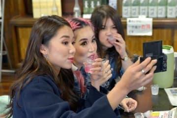 焼酎やリキュールを試飲しながら動画を撮影するシンガポールの女性ら=人吉市