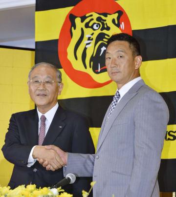 2015年10月、金本知憲監督の就任記者会見で握手する阪神の坂井信也オーナー(左)=大阪市