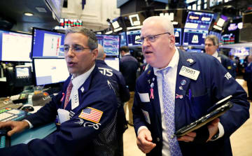 ニューヨーク証券取引所のトレーダーたち=11日(ロイター=共同)