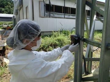 農場内の飼料タンクの柱にカメラを取り付ける都城家畜保健衛生所職員(県提供)