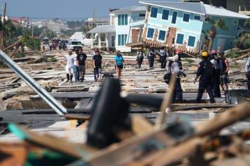 11日、大型ハリケーン「マイケル」の被害が出た米フロリダ州の大通りを歩く住民ら(ロイター=共同)