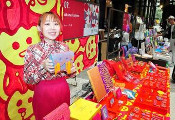 色鮮やかな刺しゅう作品を販売するアカネコジマさん=11日、大阪市北区のグランフロント大阪
