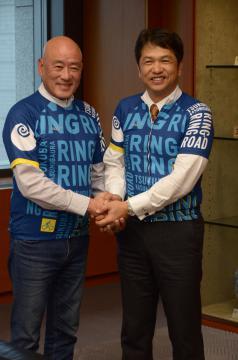 大井川和彦知事(右)と懇談後、本県のサイクルジャージー姿で握手する台湾の自転車メーカー・ジャイアントの羅祥安前社長=知事応接室
