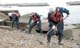 震災の爪痕が残る海岸で捜索に当たる署員