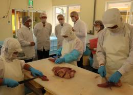 牛タンの加工作業を視察するヤコビ氏(奥左から2人目)