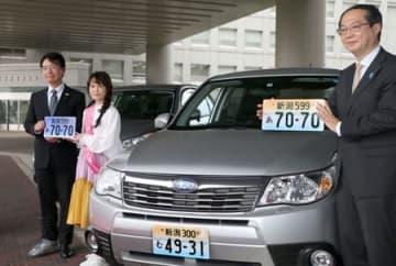 図柄入りナンバープレートをアピールするNao☆さん(左から2人目)ら=11日、県庁