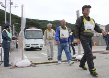 放射性物質を調べるゲート型モニターを通って、フェリー乗り場に向かう住民=12日午前10時10分、愛媛県伊方町の三崎港