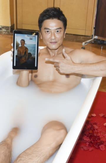 裸でバスタブに入ったまま写真集をアピールする原田龍二=12日、東京都内