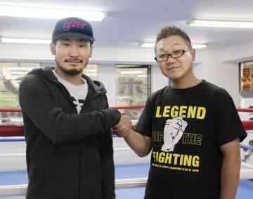 現役続行を明言し握手する岩佐亮佑(左)とセレス小林会長=12日、千葉県柏市