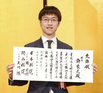 囲碁の第43期碁聖就位式で、允許状を手にする許家元新碁聖=12日午後、東京都内のホテル