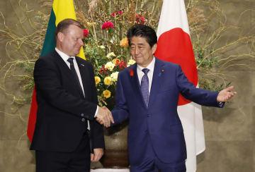 会談前にリトアニアのスクバルネリス首相(左)と握手する安倍首相=12日午後、首相官邸