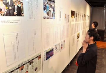 涙を浮かべながら「『言葉』展」に見入る女性=12日午後、那覇市・タイムスギャラリ-
