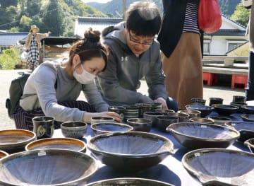 「小鹿田焼民陶祭」で陶器を手に取る人たち=13日午前、大分県日田市