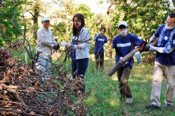 【斜面から枯木や枝を集める有志ら=四日市市西日野町の南部丘陵公園北ゾーンで】