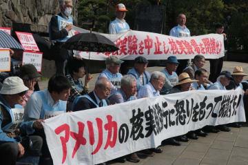 米国の臨界前核実験に抗議して座り込む被爆者ら=長崎県長崎市、平和公園