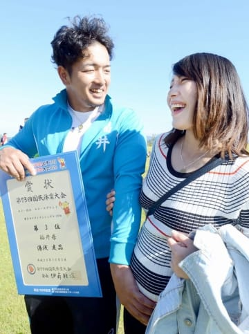 表彰式後、妻のおなかをなでながら笑顔を見せる湯浅友晶選手=10月3日、福井県あわら市の福井県立芦原青年の家