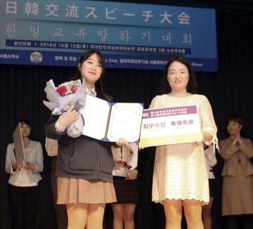 ソウルで開かれた日韓交流スピーチ大会で最優秀賞を受賞したソン・イェフンさん(左)=13日(共同)