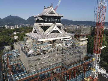 ふき替えられた屋根瓦の接ぎ目のしっくいが鮮やかな熊本城天守閣の大天守。右は最上階が足場に覆われた小天守=13日、熊本市(小型無人機から)