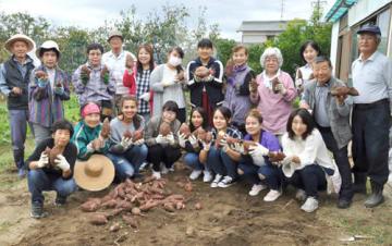 【収穫したサツマイモを手にする参加者ら=鈴鹿市江島町で】