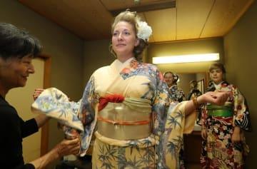 モニターツアーで着付けの体験をする外国人の参加者=長崎県佐世保市松浦町、JAさせぼホール(6月30日)