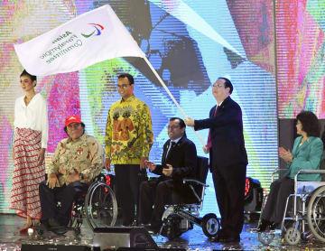 ジャカルタ・アジアパラ大会の閉会式で、次回開催地の中国・杭州の関係者に引き継がれた大会旗=13日(共同)