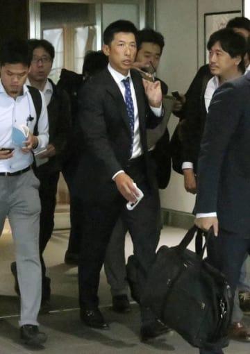 大阪空港に到着したプロ野球阪神の矢野燿大2軍監督(中央)=14日午前