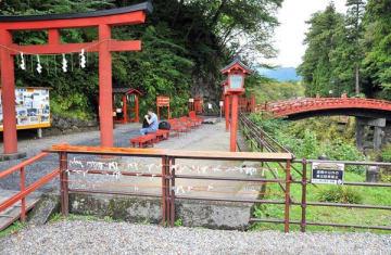 鉄パイプの柵を取り外し、朱塗りの高欄を新築する神橋境内=12日午前、日光市上鉢石町