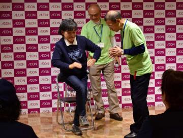 壇上で、フレイルチェックの一つ「いすからの片足立ち」に挑戦する加藤さん(左)=13日、イオンスタイル検見川浜
