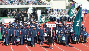 大会での活躍を誓い堂々と行進する本県選手団=13日、福井市・県営陸上競技場