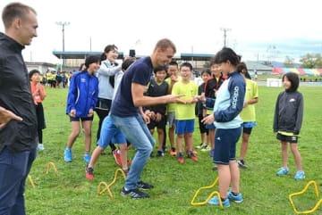 ウラジオストク市チームの選手とじゃんけんを交えた練習で盛り上がる子どもたち=13日、境港市の竜ケ山陸上競技場