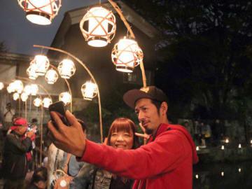 明かりに照らされた八幡堀を背景に写真を撮る人たち(近江八幡市)