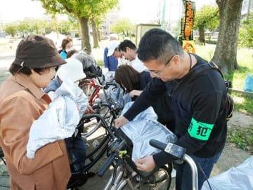 自転車の前かごにひったくり防止カバーを取り付ける署員(右)=13日、大阪市大正区の鶴町中央公園