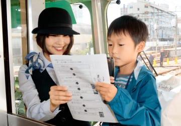 郊外電車で車内アナウンスを体験する子ども