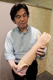 電池をセットした筋電義手を持つ陳隆明医師。外出先でも充電可能だ=神戸市西区曙町、兵庫県立福祉のまちづくり研究所
