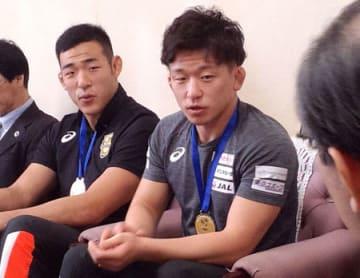 メダルを胸に、世界大学選手権の報告をする北岡選手(右)と園田選手=大津市・滋賀県庁