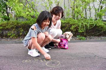 イエローチョークの使い方を実演する、花の森自治会住民の旭吉さん親子