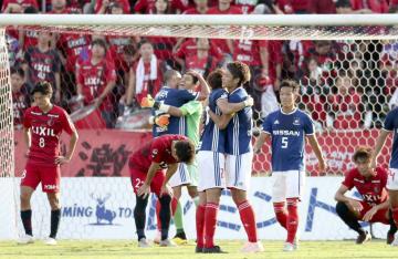 決勝進出を決め、抱き合って喜ぶ扇原(右から3人目)ら横浜Mイレブンと、肩を落とす鹿島イレブン=ニッパツ球技場