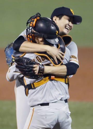 セ・リーグのCSファーストステージ第2戦でノーヒットノーランを達成し、小林誠司捕手と笑顔で抱き合う巨人の菅野智之投手=14日、神宮球場