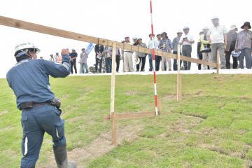 完成した堤防を見学する地元の人たち。赤白ポールが刺さったところが以前の堤防の高さ=常総市三坂町