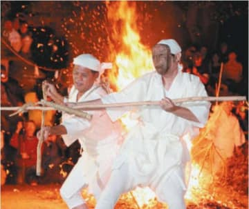 燃えるシダの炎を背に、火を守るトウバ(左)とせめぎ合うケベス=14日夜、国東市国見町