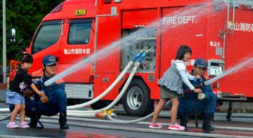 【放水体験をする子どもら=亀山市長明寺町の亀山消防署北東分署で】