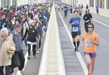 白鳥大橋を疾走するハーフマラソン参加者を見守るウオーク参加者=午前10時14分