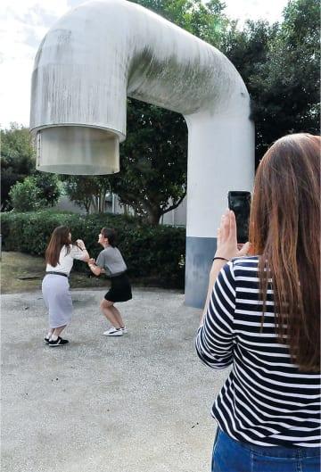 """平成町にある蛇口を想起させるモニュメントで""""インスタ映え""""を意識した写真を撮影する関学生"""